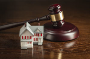 28907376 - gavel and small model house on wooden table.